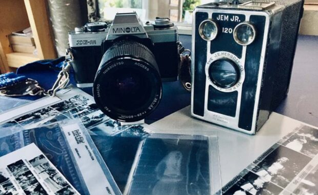Minolta XG-M and Jem Jr. cameras face viewer with developed film and digital scans of film strewn below them on a table