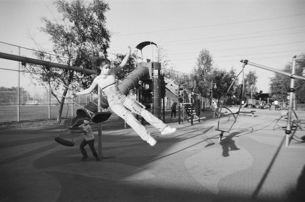 Teen white woman in jeans and a half top is flying through air as she jumps off of a swing as a young child holds his swing watching on a playground