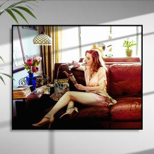 photographic print of Cass Louise sitting in profile on a dark couch with skirt askew, draped fishnet hosed legs, while sipping a Mexican Coke and reading vintage comic books.