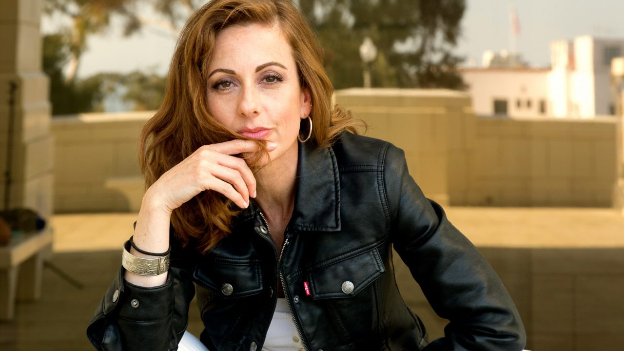 Cass Louise, an auburn haired white woman in a black leather jacket, silver hoops, and a silver bracelet gazes at viewer with a finger wrapped with some hair across her chin