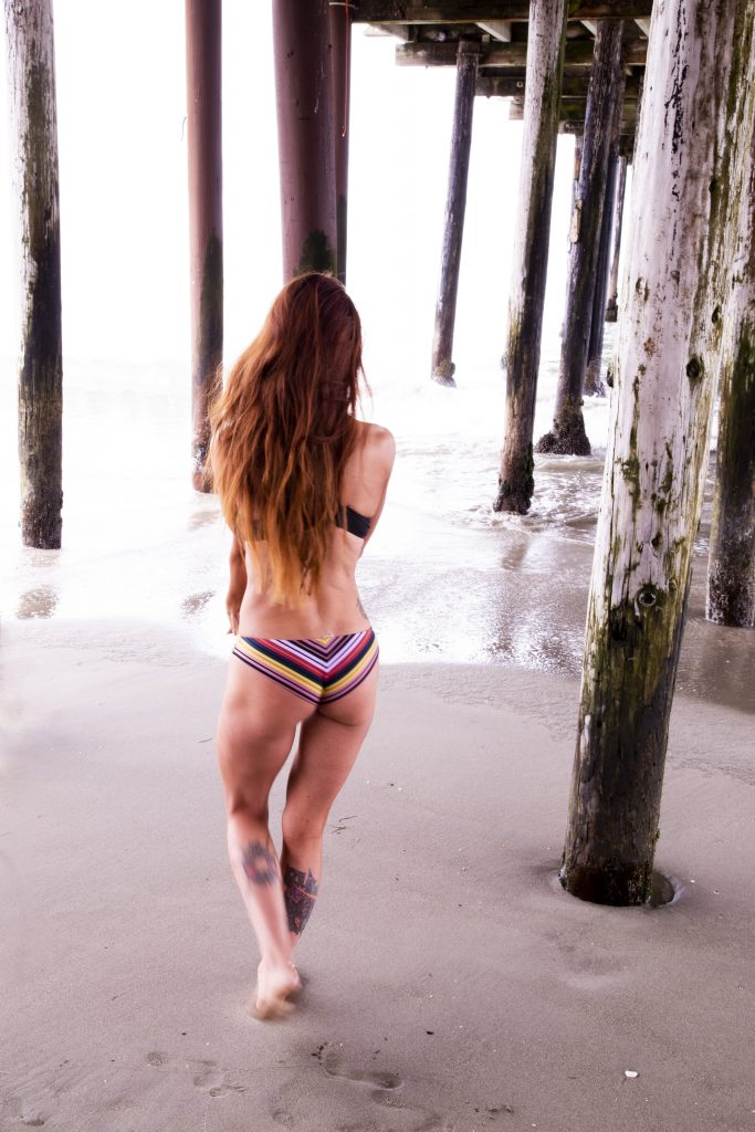 red haired white woman in a striped bikini walks away towards the shore underneath a pier