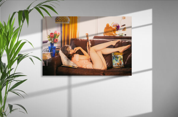 shadowy wall with hung high-gloss aluminum print of Cass Louise reclining on a leather couch in panties, fishnet hose and pink chiffon blouse, comic books strewn about, and coyly gazing at viewer.