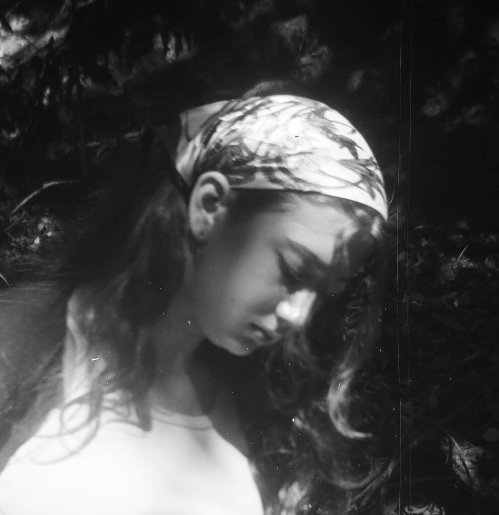 Black and White photo of dark haired teen white woman with scarf on head and white shirt looks down