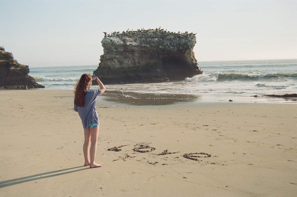 Red haired white teen woman in shorts and blue shirt peers out over ocean standing by the word Love written in sand at beach with large pelican covered rocks and waves in the background