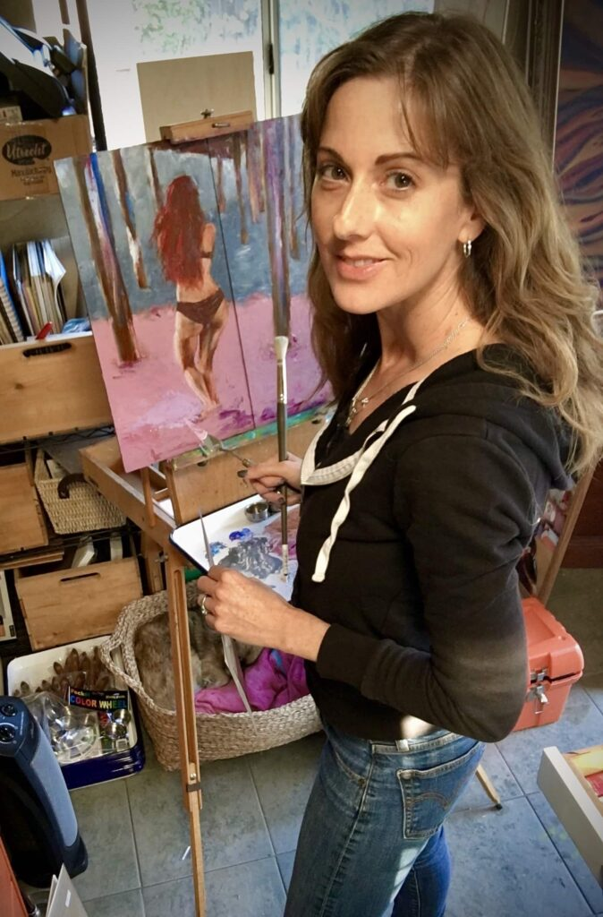 Cass Louise, a white woman in a black hoodie and jeans turns to pose and smile as she stands at an easel in her studio painting a bikini clad woman on a beach under the pier in pinks, greens, browns and blues.