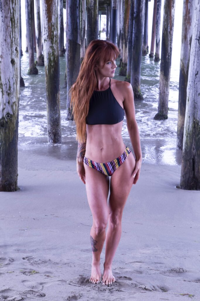 Redhaired white woman in black bikini top and striped bottoms poses in front of piers on beach gazing sideways